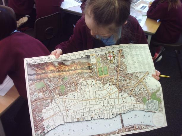 Maisie using a map to look at London in 1666